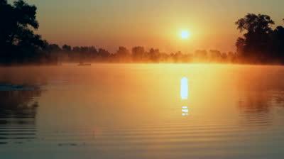 stock-footage-sunrise-on-the-lake-sunrise-over-river-fisherman-on-the-boat-on-the-sunrise-morning-landscape