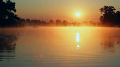 stock-footage-sunrise-on-the-lake-sunrise-over-river-fisherman-on-the-boat-on-the-sunrise-morning-landscape