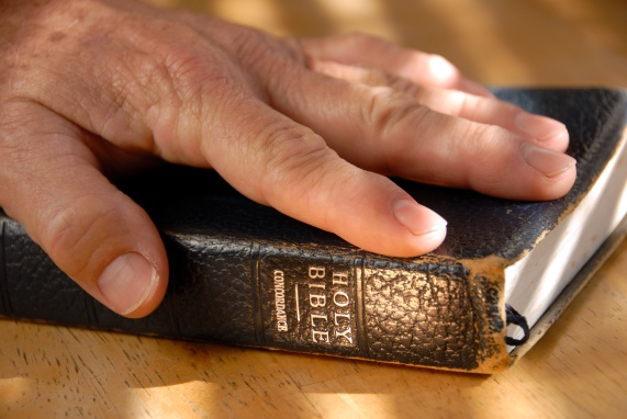 Hand On Well Used Old Bible Under Painted Light